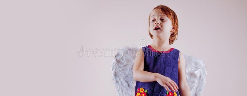 天使跳舞 小逗人喜爱的儿童女孩画象有天使翼的 免版税图库摄影