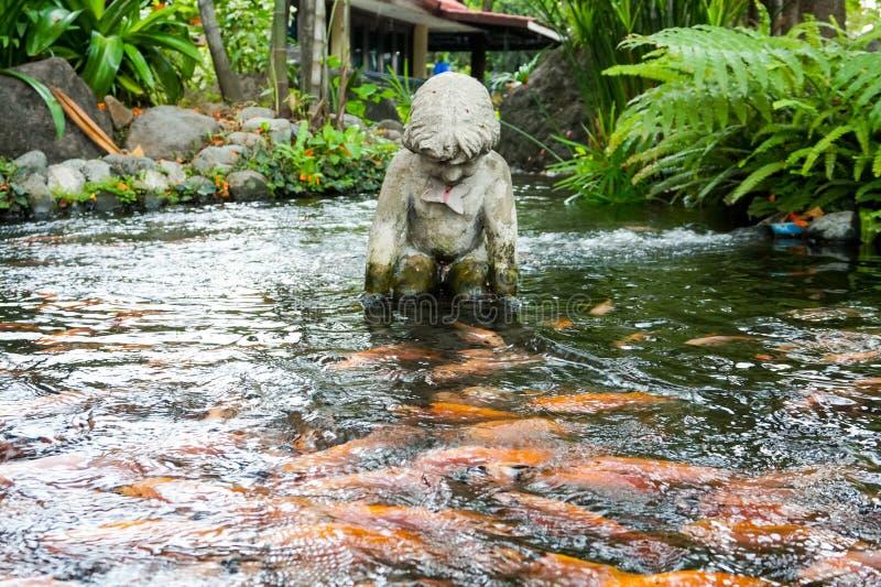 天使雕象在池塘 免版税图库摄影