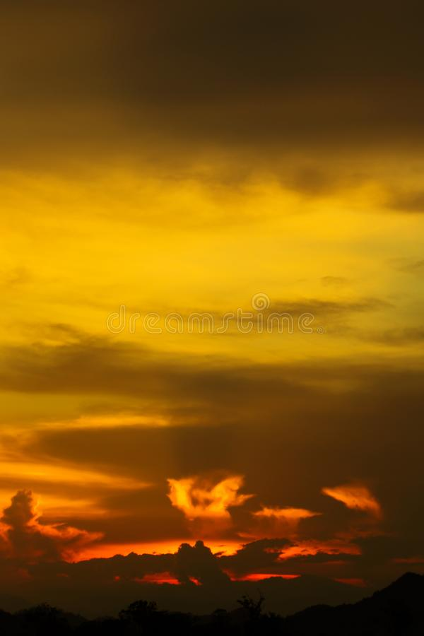 天堂五颜六色的云彩的地狱现出轮廓与光的蓝天背景金黄日落发光通过云彩 库存图片