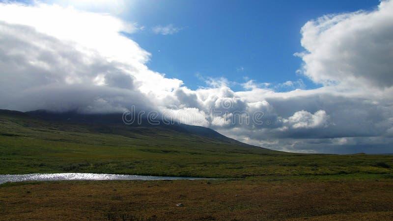 天太阳光芒刺穿了厚实云彩,拥抱山,撒布与绿草和用山装饰 免版税库存照片