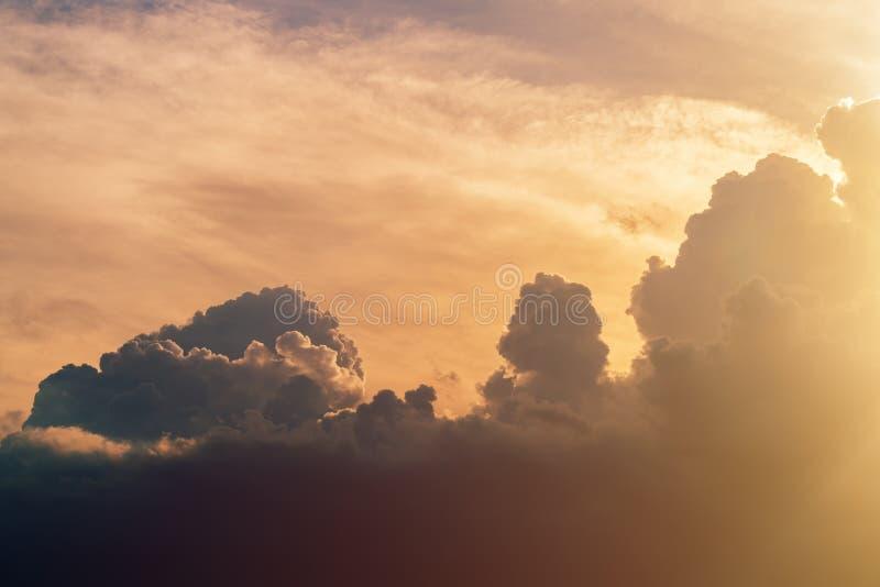 天气和气候变化,阳光通过黑暗的风雨如磐的云彩 免版税库存照片