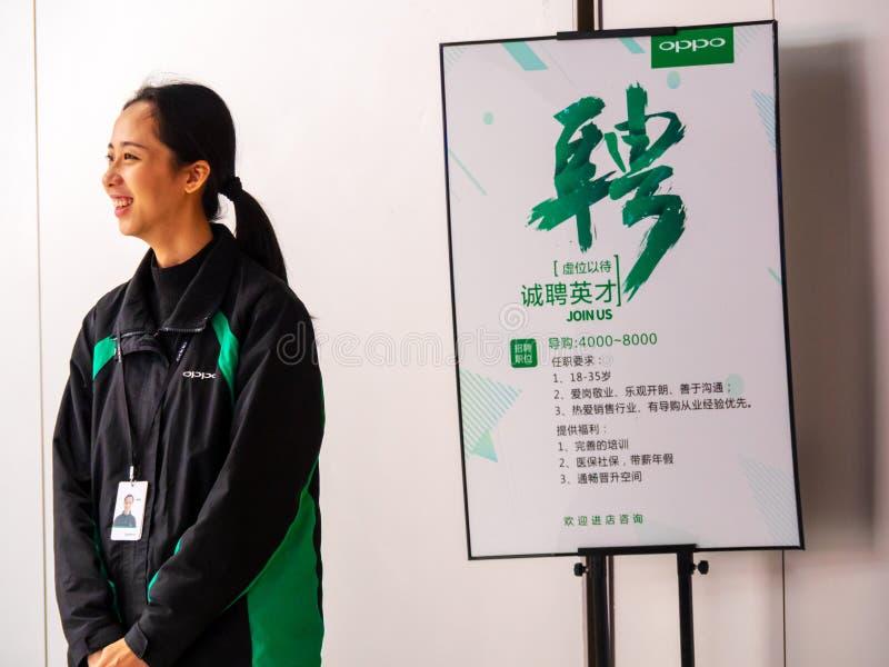 天河,广州市,中国- 2019年3月7日-一名微笑的Oppo雇员在职员补充海报寻找的销售旁边站立 库存照片