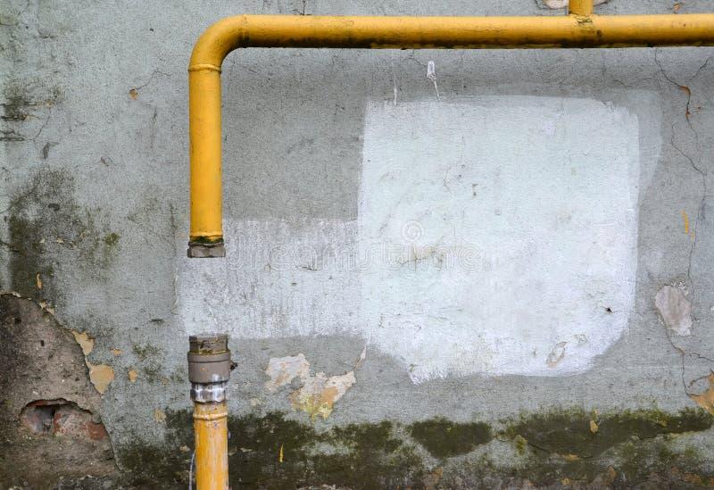 天然气切除在疏忽的一个公寓里能由居民支付债务 在大厦门面的一根煤气管 库存图片