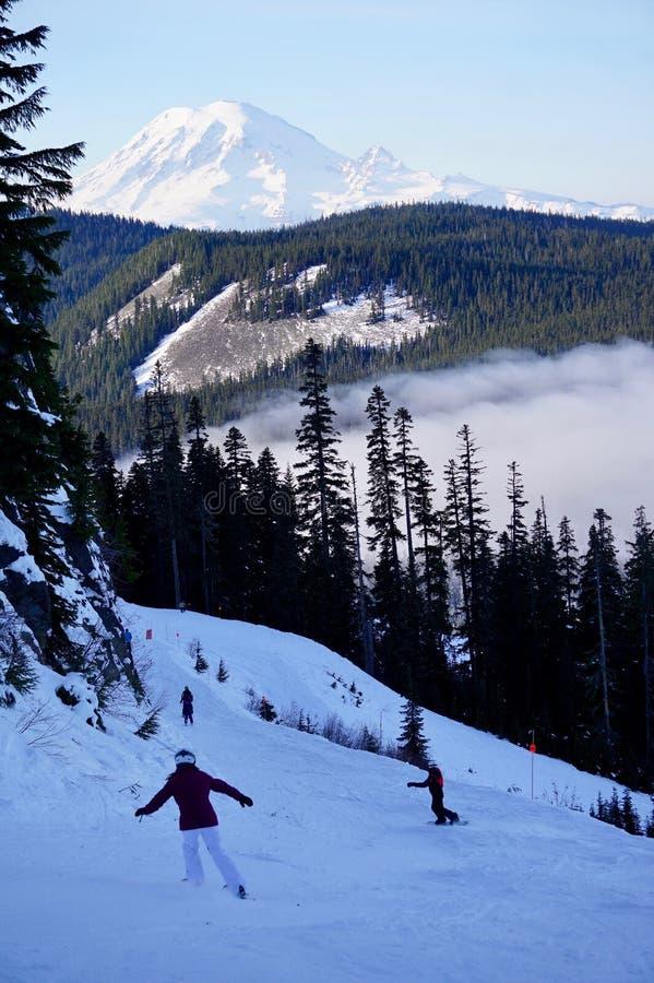 天的前奔跑:滑雪者&挡雪板& Mt 从白色通行证看见的更加多雨,WA 免版税库存图片