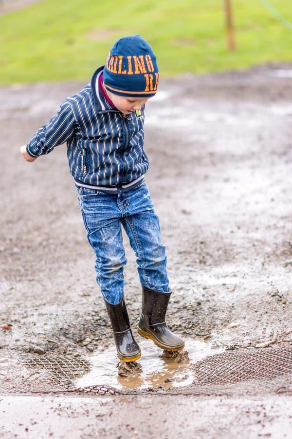 天看法激动的男孩在水坑跳 免版税库存图片