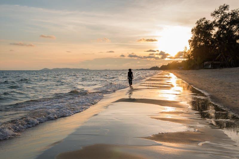 天空和海日落的 走在海洋海滩的少妇剪影 免版税库存照片