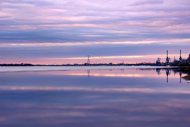 天空的美好的反射在日落的在河的水中 背景蒲公英充分的草甸春天黄色 库存照片