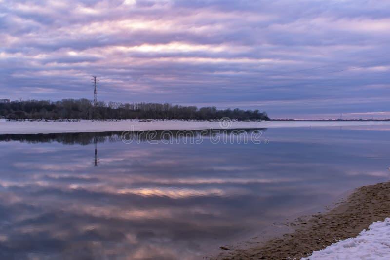 天空的美好的反射在日落的在河的水中 背景蒲公英充分的草甸春天黄色 免版税库存图片