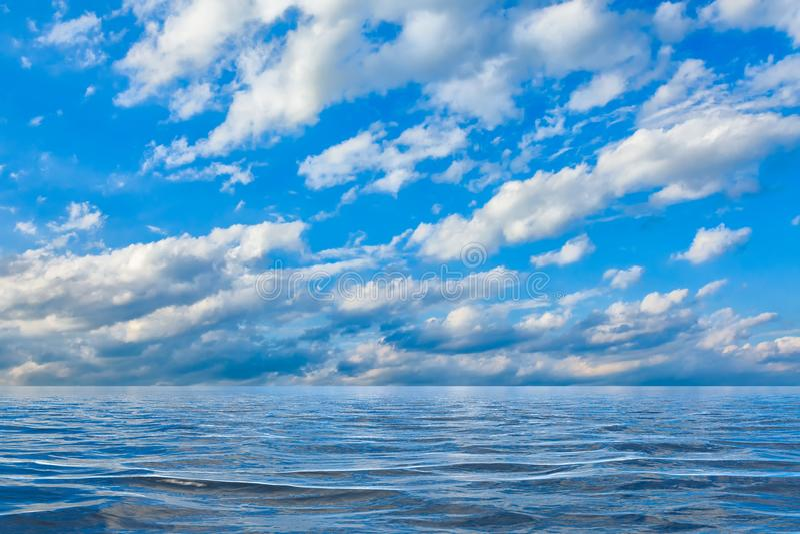 天空背景与云彩的在水或海洋反射了 免版税图库摄影