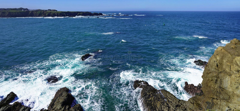 天空蔚蓝和海海岸线风景全景与岩石的太平洋海岸的 图库摄影