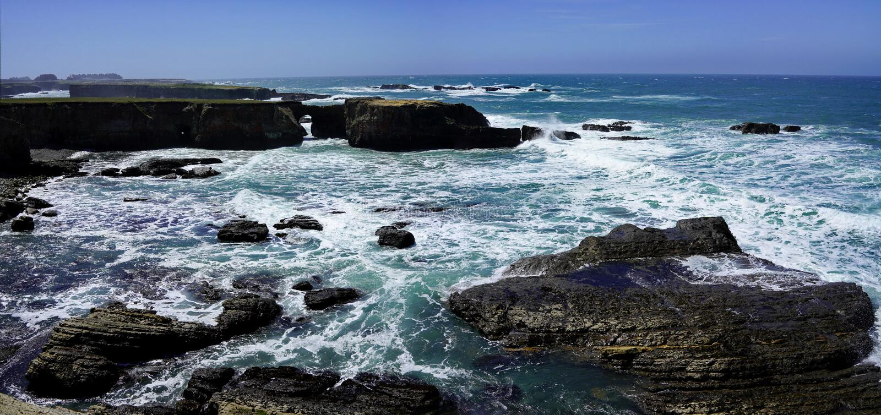 天空蔚蓝和海滩海岸线风景全景与岩石的在太平洋海岸的 图库摄影