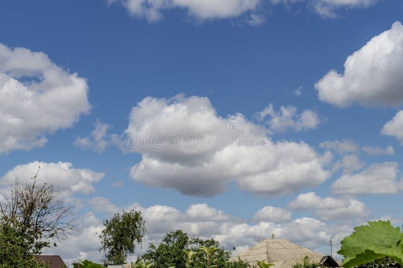 天空蔚蓝和美丽的云彩与村庄的房子屋顶  夏天海报的简单的风景背景 浩大的天空蔚蓝 库存照片