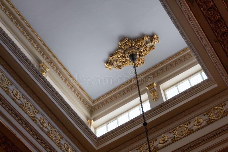 天窗窗口阐明的天花板显露精心制作的檐口和带状装饰工作,丰富的金叶 免版税库存照片
