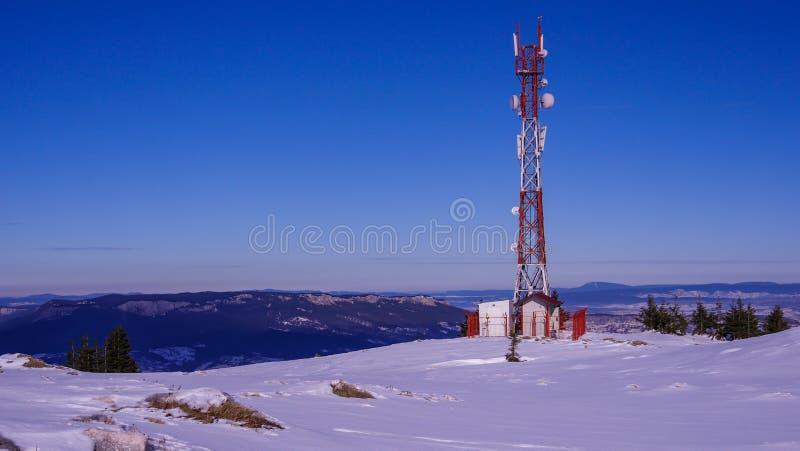 天线在多雪的山顶部的中继器塔 免版税库存图片