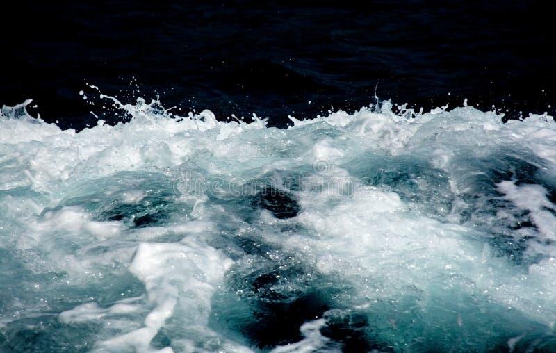 天蓝色和白色小船苏醒seafoam 库存照片