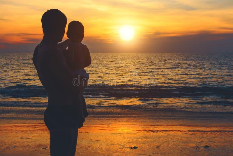 天蓝色的海的岸的注意日落的父亲和儿子 生活方式,假期,幸福,喜悦概念 娱乐活动 免版税库存照片