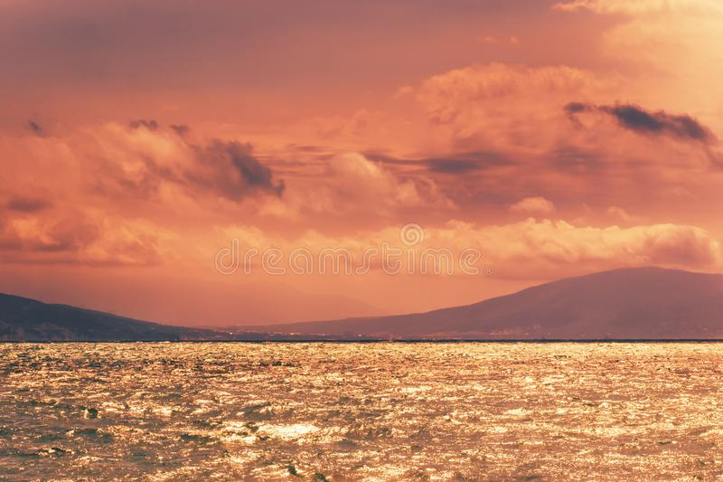 天蓝色的海,山,在日落的橙色金黄天空 夏天海风景风景在晴朗的晚上 库存照片