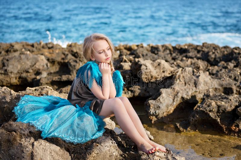 天蓝色的礼服的沉思女孩有尾巴的喜欢鸟坐海洋海的岩石海岸 库存照片