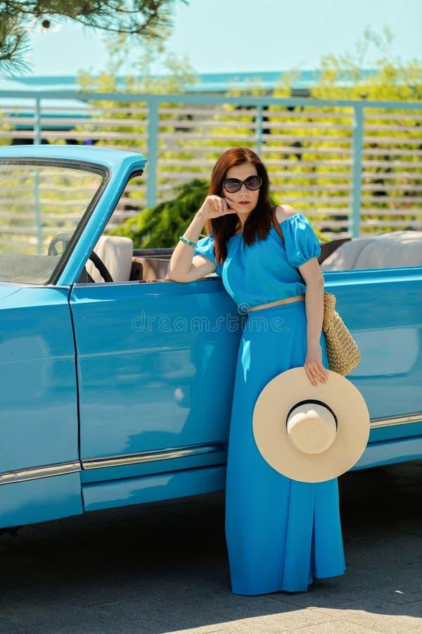 天蓝色的长的礼服的年轻美丽的妇女在一辆减速火箭的汽车附近 库存照片