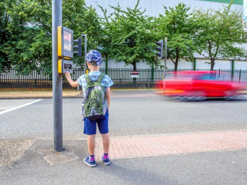 天视图有按步行信号按钮的背包的小孩男孩穿过英国路 免版税库存图片