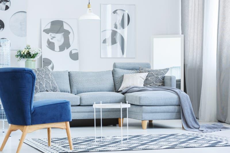 天鹅绒扶手椅子在灰色屋子里 免版税库存照片
