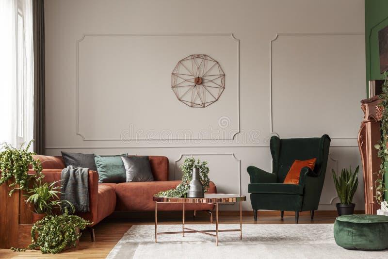 天鹅绒有橙色枕头的鲜绿色扶手椅子 库存照片
