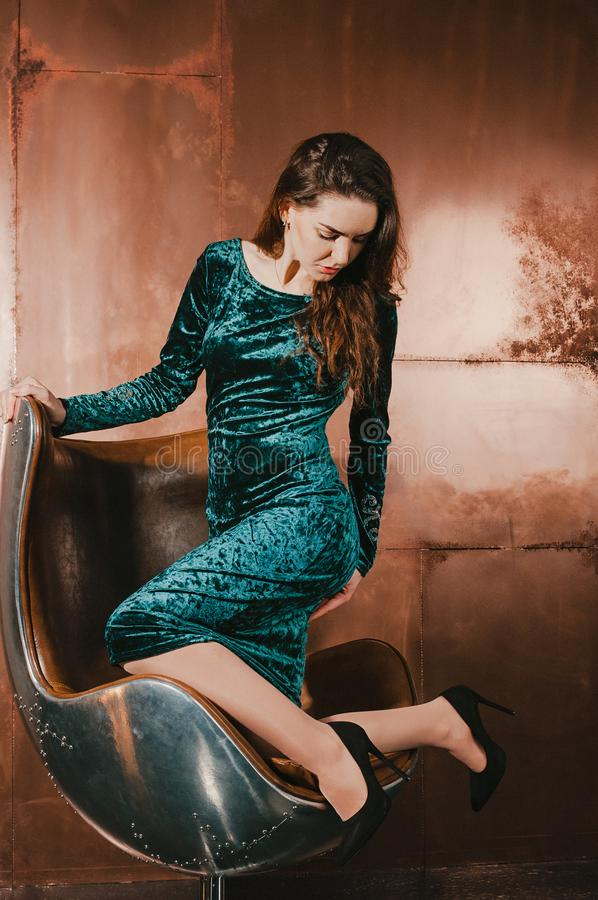 天鹅绒礼服的可爱的少妇,坐在皮革b 免版税库存照片
