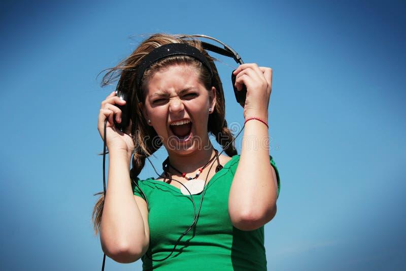 太大声佩带耳机的女孩 库存图片