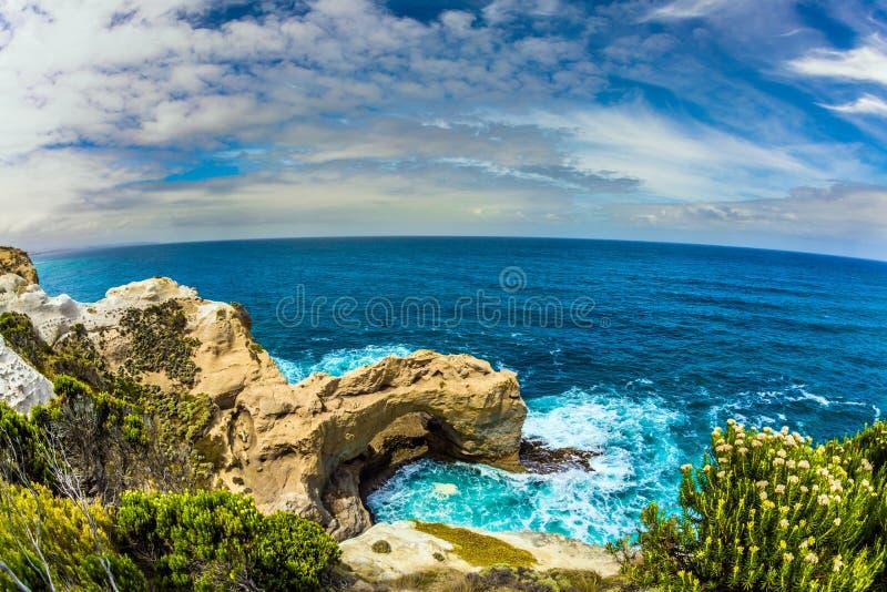 太平洋波浪在岸碰撞下来 沿海岩石形成了砂岩美丽如画的曲拱  澳大利亚的大洋路 图库摄影