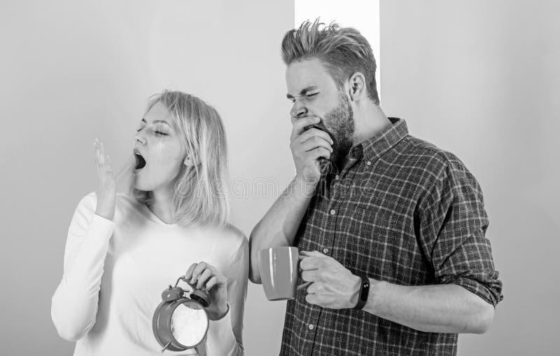 太早唤醒 夫妇睡觉没有足够时间 家庭饮料早晨咖啡打呵欠的面孔 唤醒怨恨的早晨 免版税库存图片