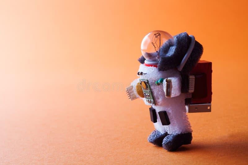 太空人电灯泡字符在太空服和宇航员弹药穿戴了 宇航员走的抽象橙色行星 免版税库存图片