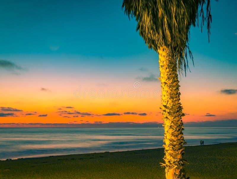 太阳下来上色天空和海洋 免版税库存图片