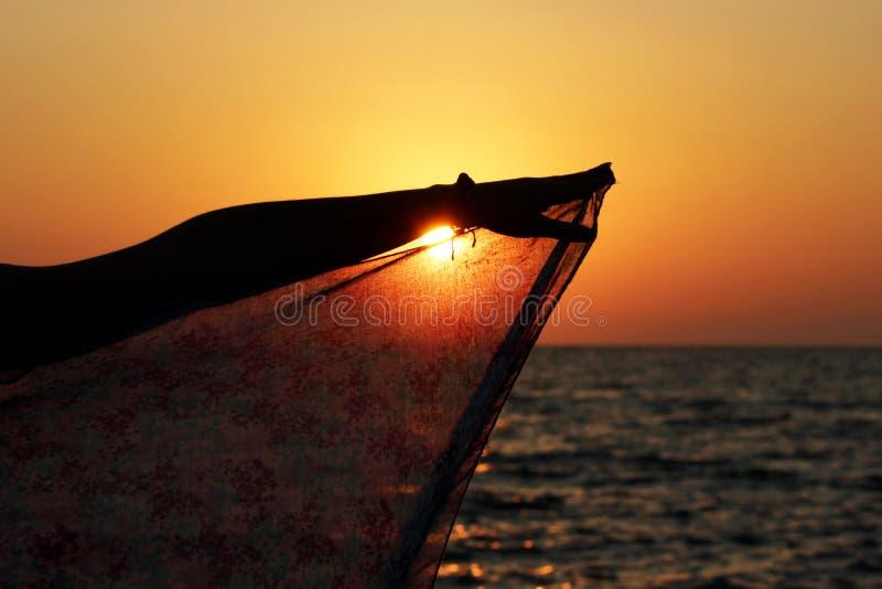 太阳下降入海在日落并且通过pareo的围巾发光,由年轻人的手举行 免版税库存照片