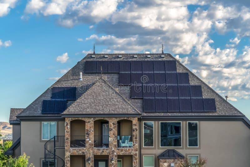 太阳供给动力的家的门面有上升至阳台的螺旋形楼梯的 免版税库存图片
