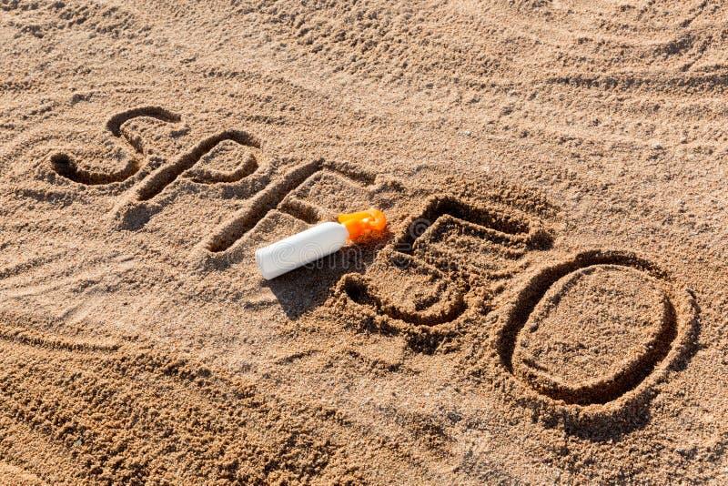 太阳保护因素五十 在沙子和白色瓶写的SPF 50词有晒黑奶油的 皮肤护理概念背景 库存照片