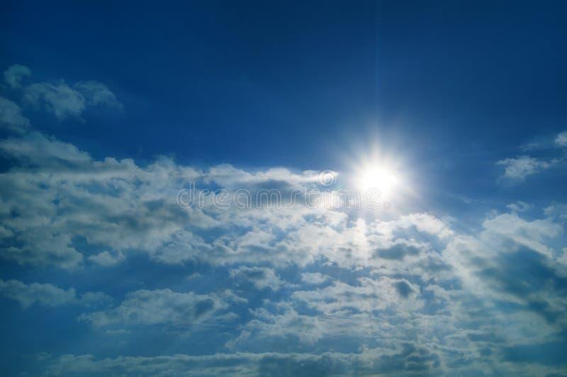 太阳光芒与云彩的反对蓝天 免版税库存照片