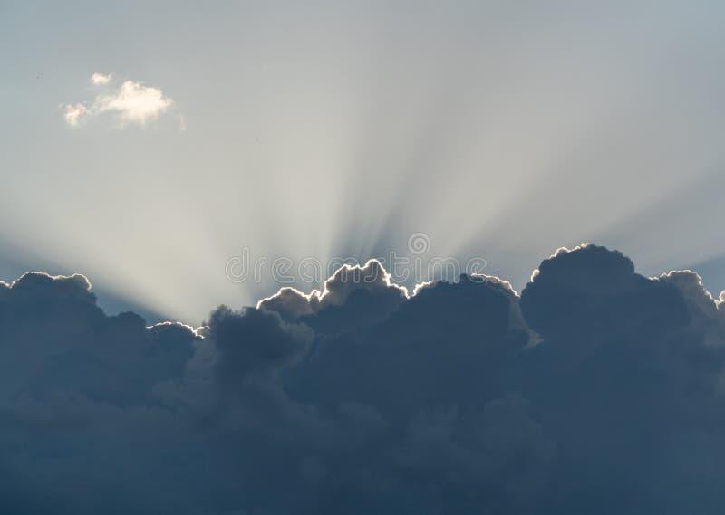 太阳光芒从在天空蔚蓝的后面云彩 库存照片