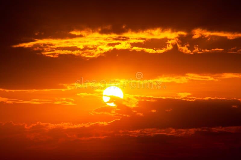太阳光芒是下来和惊人的剧烈的橙色云彩,微明 免版税库存照片
