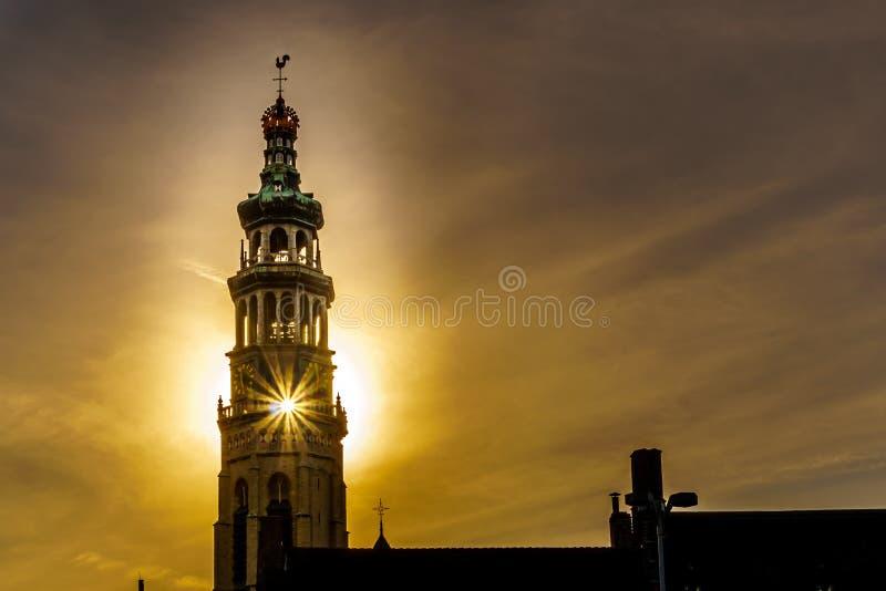 太阳光芒通过中世纪修道院的兰吉约翰1月Toren长的塔从太阳设置的在塔后在米德尔堡 免版税库存照片