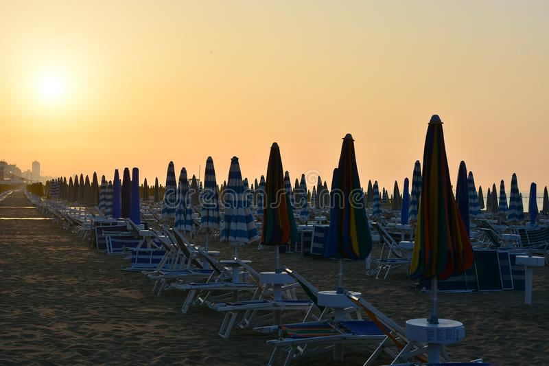 太阳升起,照亮海滩,沙滩伞,空的deckchairs 免版税库存照片