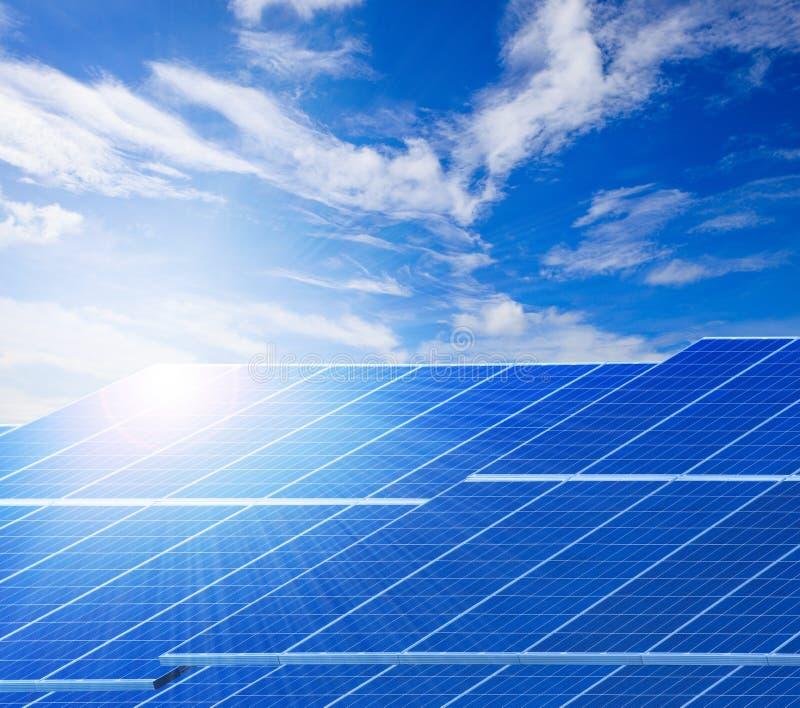 太阳反对美丽的清楚的蓝色sk的光和太阳能电池盘区 图库摄影