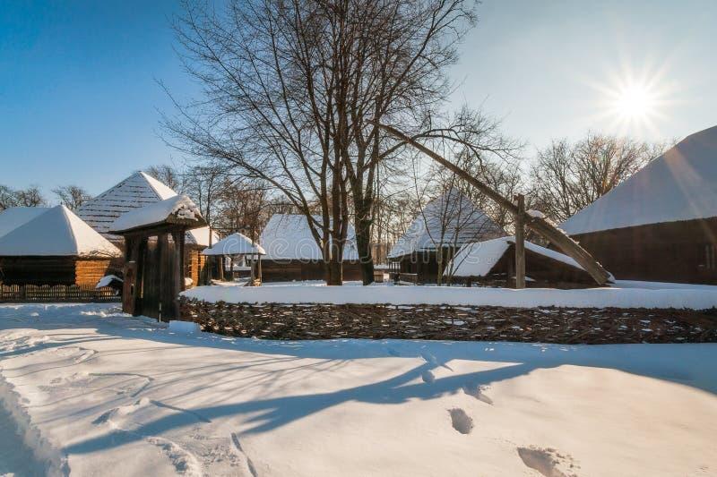 太阳发光在一个传统罗马尼亚村庄在冬天 图库摄影
