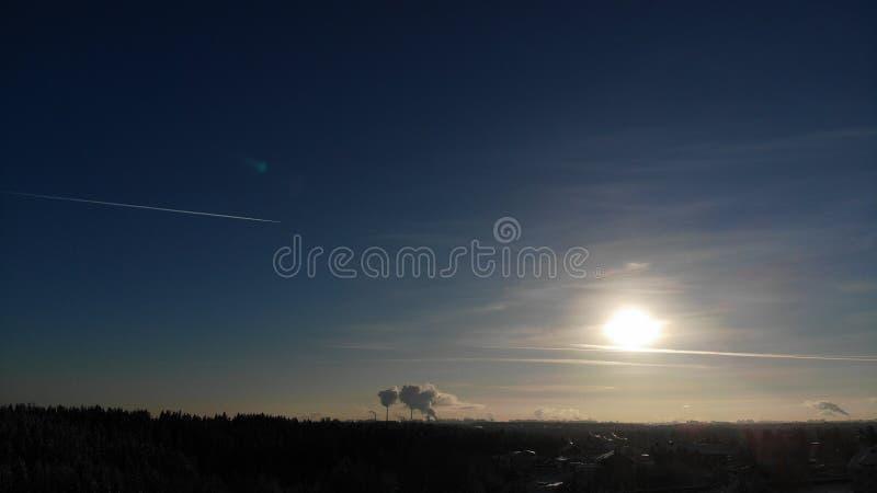太阳发光烟的一清楚的冷淡的天从发电站的管子上升概略的看法 俄罗斯圣彼德堡reg 免版税图库摄影