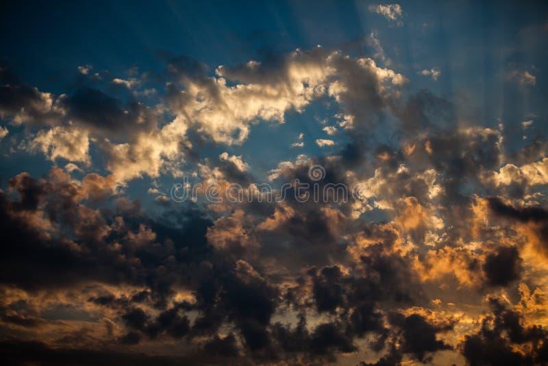 太阳发出光线做他们的方式通过褴褛蓬松云彩 图库摄影