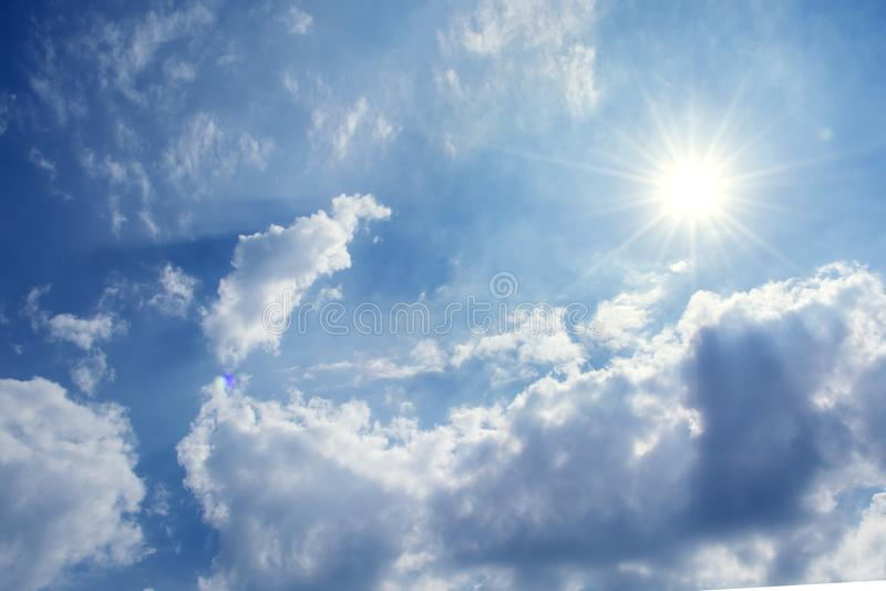 太阳发出光线反对在云彩的蓝天, 免版税图库摄影