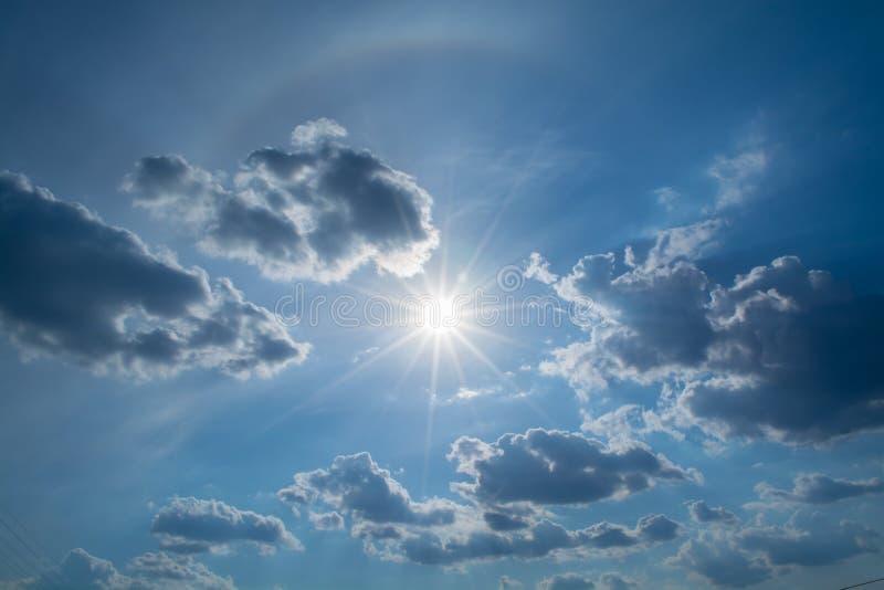 太阳发出光线反对在云彩的蓝天 免版税库存照片