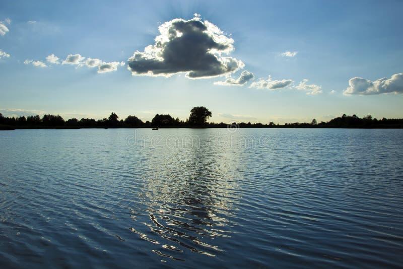 太阳在云彩后掩藏由湖 图库摄影