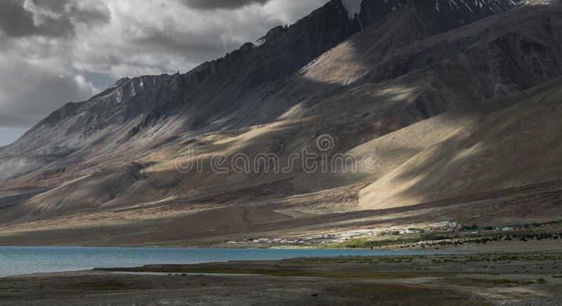 太阳在小村庄的射线下落在山脉的乡下周围 免版税库存照片