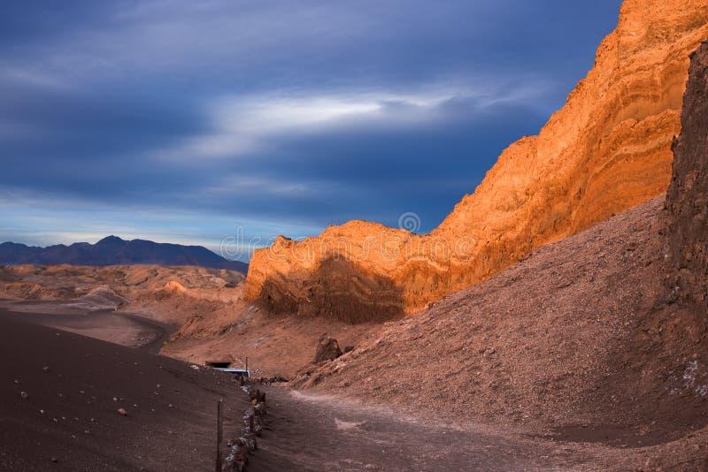 太阳在月亮谷的岩石峭壁美妙地设置在阿塔卡马沙漠,当阴暗由风雨如磐的天空时 库存照片