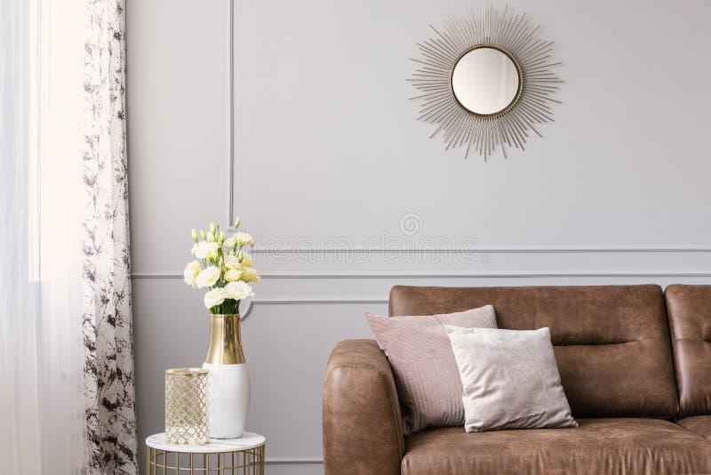 太阳在灰色典雅的客厅喜欢在皮革沙发上的形状的镜子有枕头的 免版税库存照片